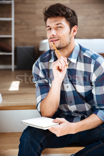 Stock photo: Thoughtful young man with notepad sitting and thinking at home