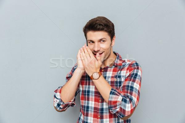 Souriant jeune homme parler secrets téléphone portable gris Photo stock © deandrobot