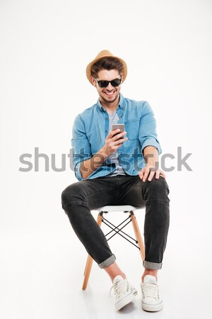 Pensativo joven sombrero gafas de sol sesión silla Foto stock © deandrobot