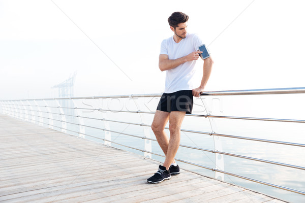 Male athlete with armband using blank screen smartphone Stock photo © deandrobot