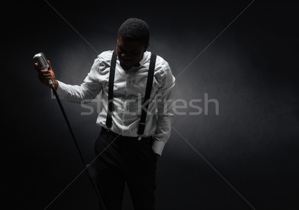 Male singer posing over dark background Stock photo © deandrobot
