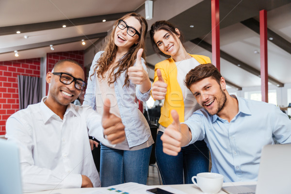 Smiling business people showing thumbs up working in office Stock photo © deandrobot