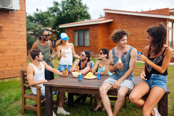 Happy young people drinking beer and having outdoor summer party Stock photo © deandrobot