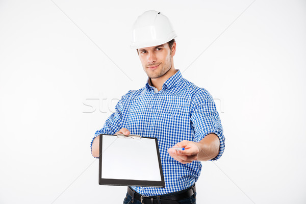 Confident young man building engineer in helmet holding blank clipboard Stock photo © deandrobot