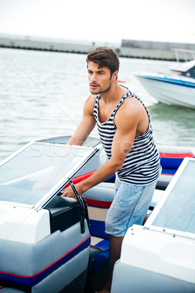 Young handsome sailor man driving his motor boat Stock photo © deandrobot