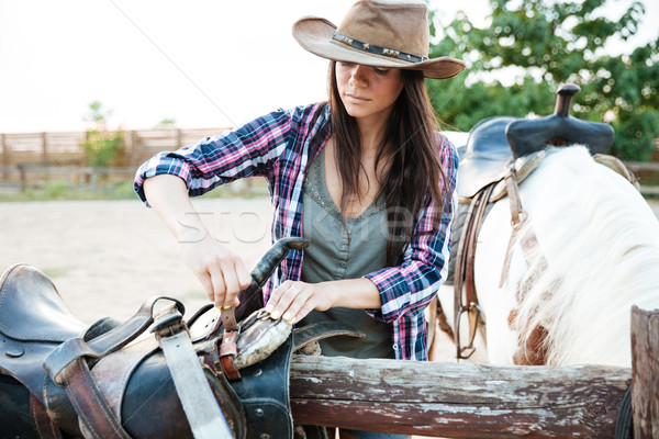 Woman cowgirl in hat preparing saddle for riding horse Stock photo © deandrobot