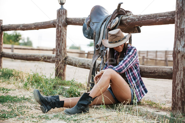 Pretty cowgirl resting while leaning on the ranch fence Stock photo © deandrobot