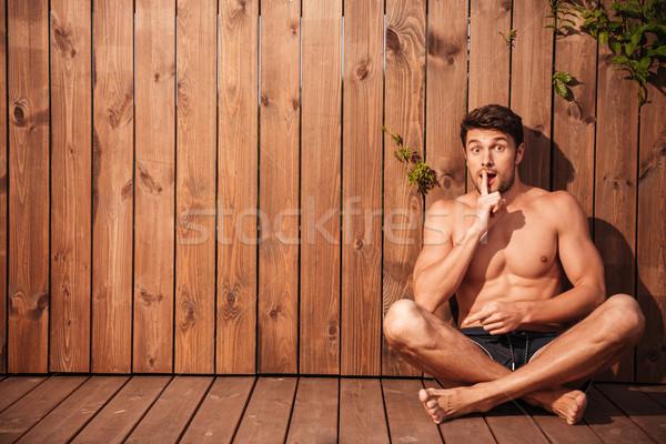 Bonito jovem animado homem sessão Foto stock © deandrobot