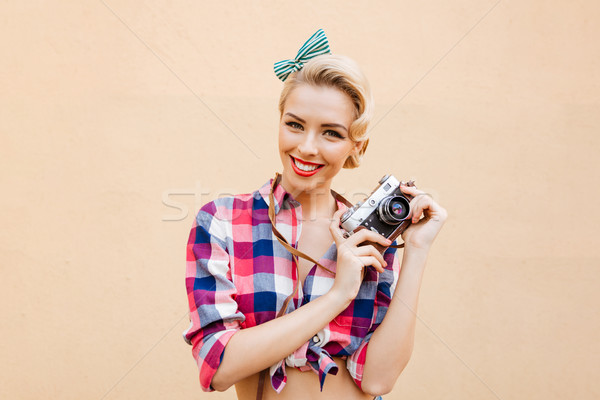 Happy smiling pinup girl in yellow dress using vintage camera Stock photo © deandrobot