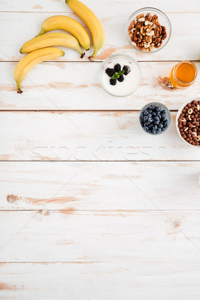 Bananas, berries, walnuts and honey on wooden background Stock photo © deandrobot