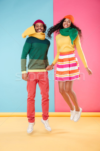 Cheerful african couple in hats and scarves jumping together Stock photo © deandrobot