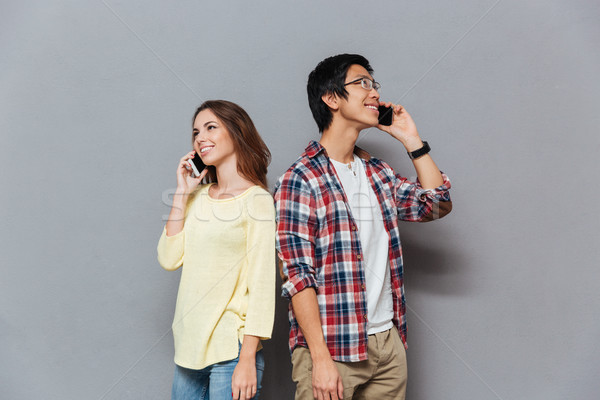 Portrait of a young multiracial couple talking on mobile phones Stock photo © deandrobot