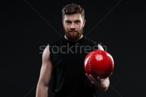 Smiling trainer with ball in hand Stock photo © deandrobot