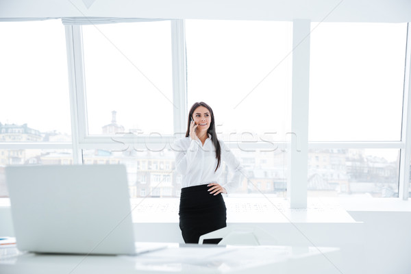 Business woman talking at phone in office Stock photo © deandrobot