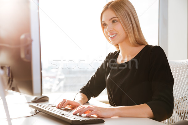 Joyful young woman worker typing by keyboard. Stock photo © deandrobot