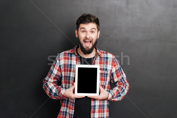 Man showing display of tablet computer to camera Stock photo © deandrobot
