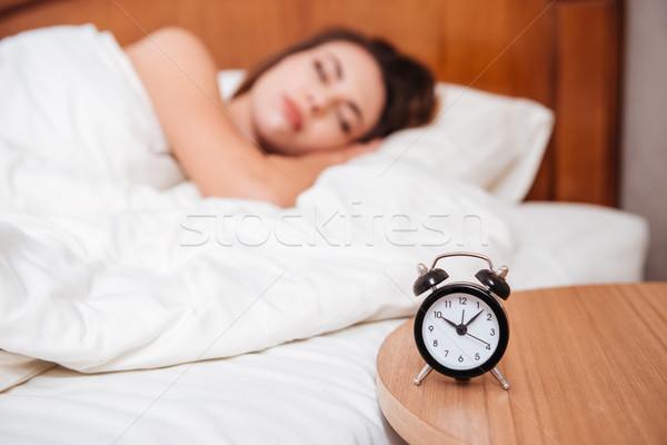 Fiatal nő alszik ágy hálószoba fókusz ébresztőóra Stock fotó © deandrobot