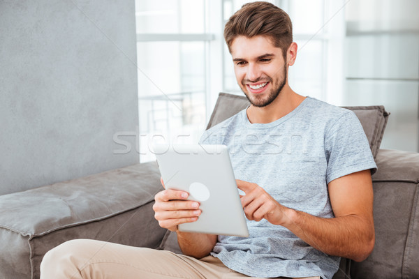 Happy man sitting on sofa and chatting by tablet Stock photo © deandrobot