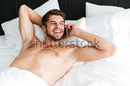 Stock photo: Amazed shocked young man using cell phone in bed