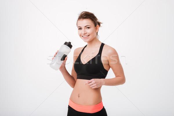 улыбаясь Фитнес-женщины фляга указывая пальца Сток-фото © deandrobot