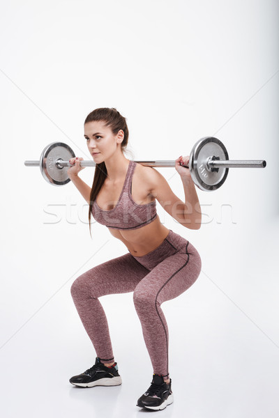 Portrait of a focused fitness woman doing squats with barbell Stock photo © deandrobot