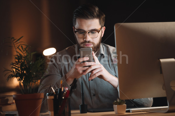 Attractive designer working late at night and chatting by phone. Stock photo © deandrobot