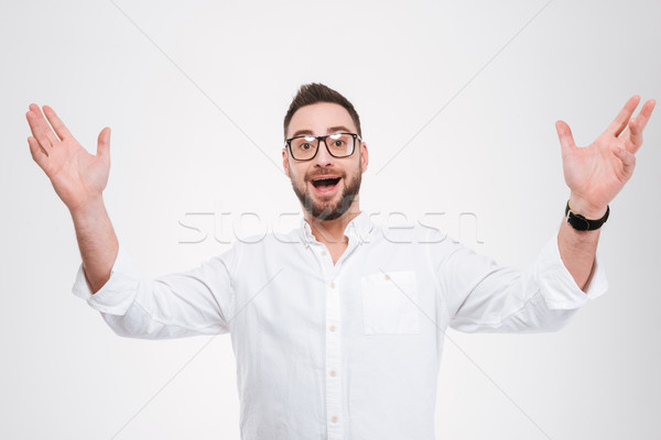 Happy young bearded man gesturing with hands Stock photo © deandrobot