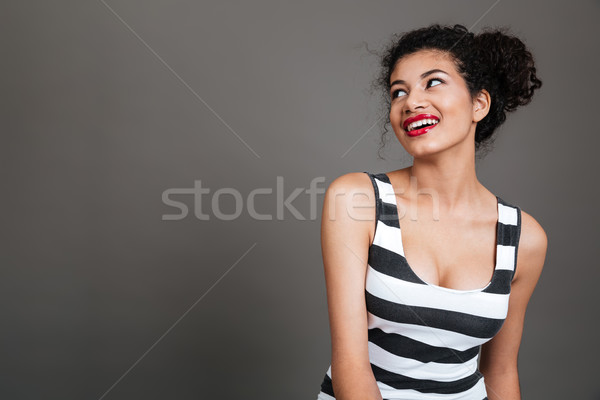 Portrait of a smiling cheerful african woman looking away Stock photo © deandrobot