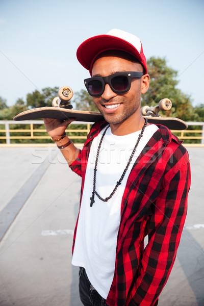 Young dark skinned guy wearing sunglasses holding skateboard Stock photo © deandrobot