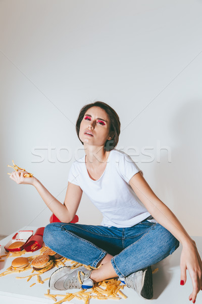 Woman sitting on the table and holding french fries Stock photo © deandrobot