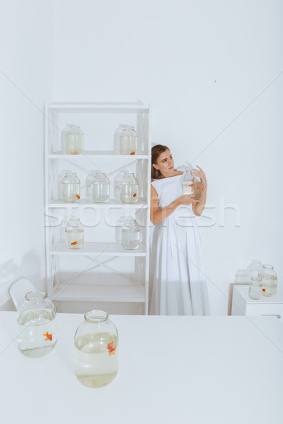 Woman standing in room and holding gold fish in jar Stock photo © deandrobot