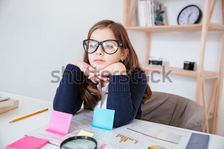 Serious little girl in glasses using tablet and sticky notes Stock photo © deandrobot