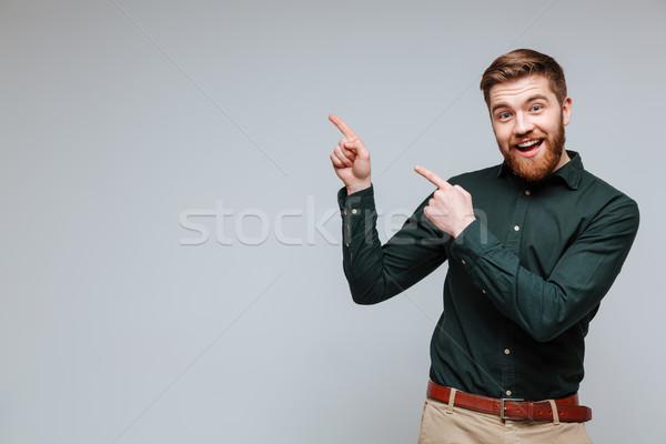 счастливым бородатый человека рубашку указывая вверх Сток-фото © deandrobot