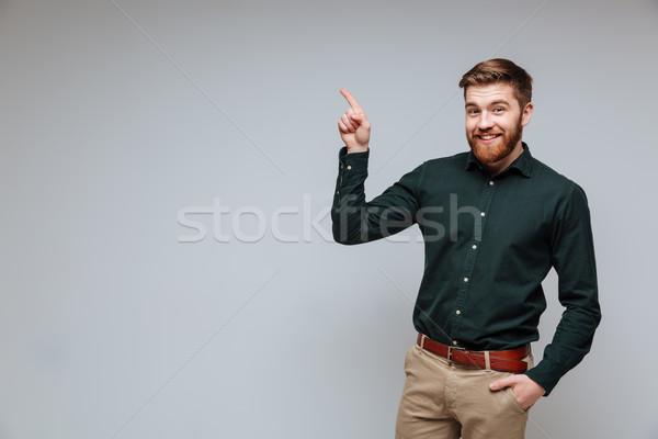 Foto stock: Sorridente · barbudo · homem · camisas · indicação · para · cima