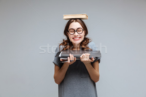 Smiling Female nerd with book on head Stock photo © deandrobot