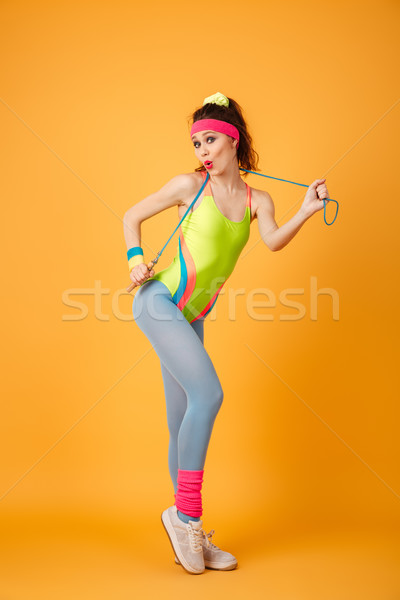 Cute lovely young fitness woman doing exercises using jumping rope Stock photo © deandrobot