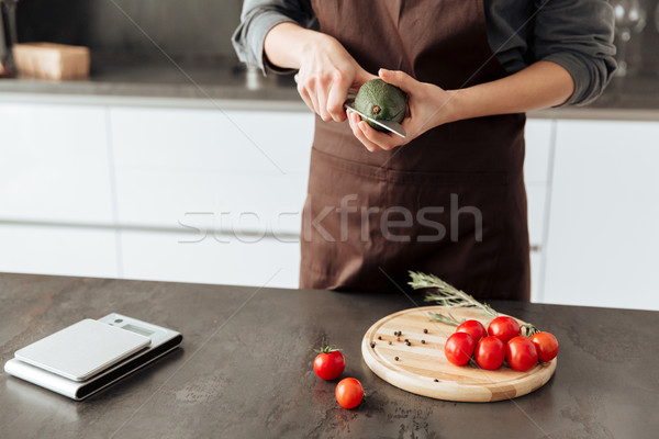 Cropped picture of young woman cut tomatoes and avocado. Stock photo © deandrobot