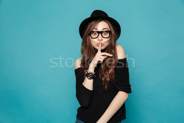 Stock photo: Woman in hat showing silence gesture and looking at camera