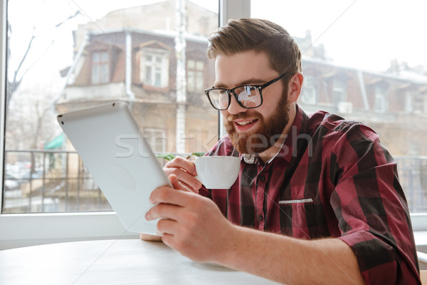 Attractive bearded young man using tablet computer. Stock photo © deandrobot