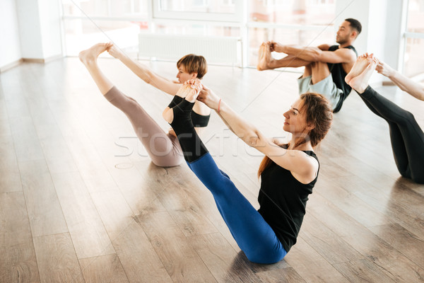Group of people stretching legs and practicing yoga in studio Stock photo © deandrobot
