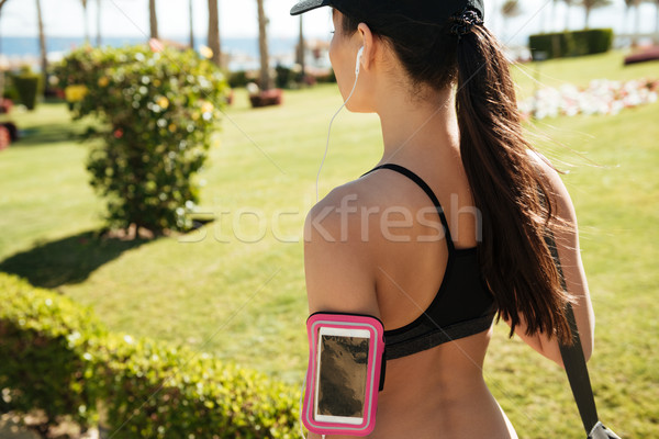 Woman athlete with balnk screen smarrtphone inside armband in summer Stock photo © deandrobot