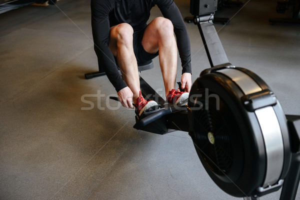 Cropped image of athletic man using rowing machine Stock photo © deandrobot