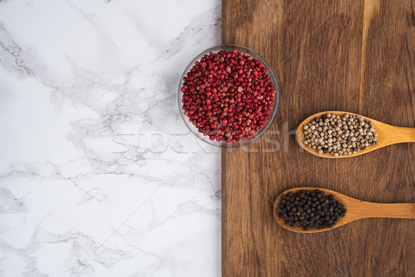Top view of assorted spices in wooden spoons on a cutting board Stock photo © deandrobot