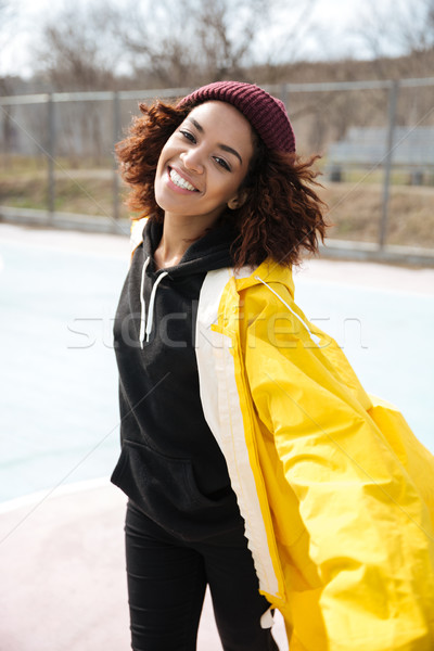 Happy african curly young lady wearing yellow coat Stock photo © deandrobot