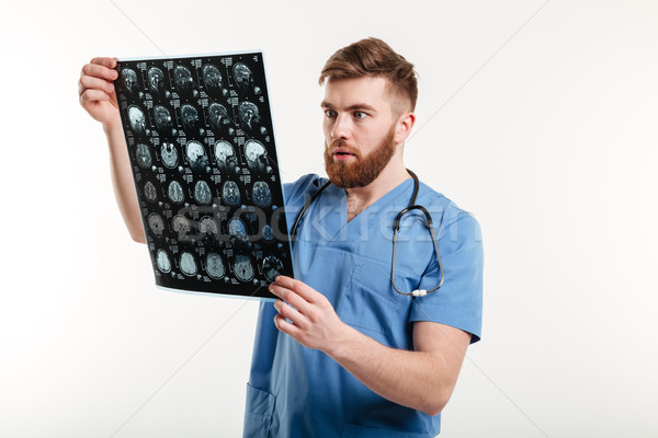 Portrait of a shocked medical doctor looking at CT scan Stock photo © deandrobot
