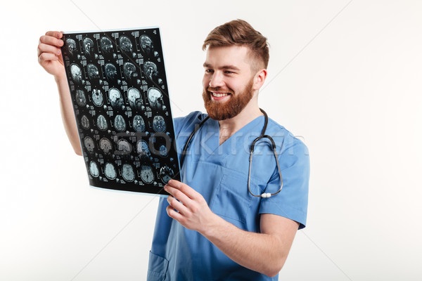Portrait of a smiling medical doctor looking at CT scan Stock photo © deandrobot