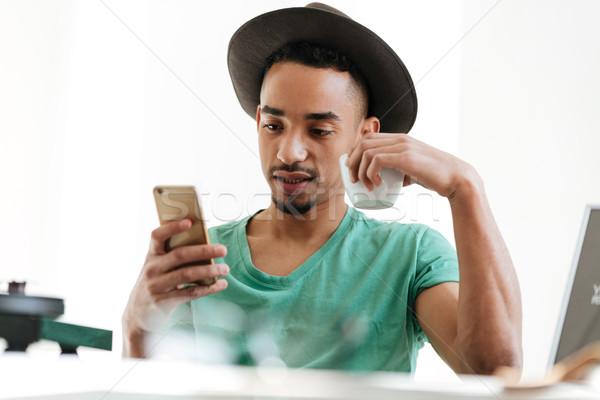 Afryki człowiek tshirt smartphone hat posiedzenia Zdjęcia stock © deandrobot