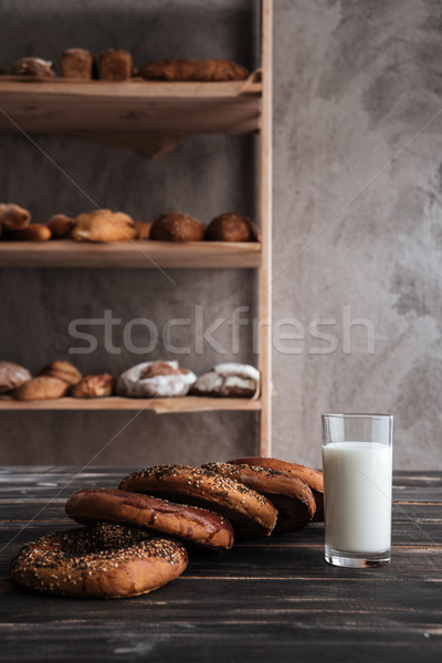 Pastries and glass of milk on dark wooden table Stock photo © deandrobot