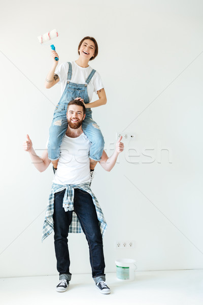 Young laughing couple holding paint rollers and looking at camera Stock photo © deandrobot