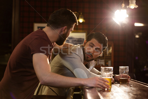 Young man helping his drunk friend Stock photo © deandrobot
